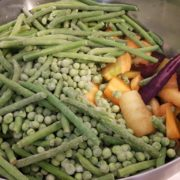 Pendant la cuisson de l'agneau, écossez les petits pois, effilez les haricots verts, rincez et brossez le reste des carottes, pelez les navets et découpez-les en morceaux. Rincez les oignons nouveaux, retirez la première peau, coupez-en les fanes, mais laissez le bulbe entier. Ajoutez ces légumes dans la cocotte avec la viande et comptez encore 30 minutes de cuisson.