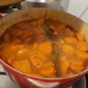 Epluchez les gousses d'ail, coupez-les en deux et retirez-en les germes, puis ajoutez-les dans la cocotte, ainsi que les carottes en rondelles et le bouquet garni.