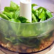 Retirer le germe de l'ail, et ajoutez-le dans le bol d'un hachoir, ainsi que les pignons de pin et de belles feuilles de basilic lavées et séchées.