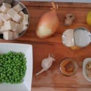 Epluchez et hâchez l'oignon en petits morceaux, épluchez le gingembre et l'ail, et émincez-les finement, rincez et tranchez la citronnelle en rondelles. Coupez le tofu en cubes de la taille d'un gros dé. Rincez et hâchez la coriandre finement.