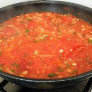 Faites revenir l'oignon en lamelles, ajoutez les tomates écrasées, l'ail, le sel, ainsi que le basilic. Faites cuire à feu doux et à découvert à la poêle. Arrêtez la cuisson avant qu'il n'y ait plus de jus. Pour que les cannelloni soient tendres, il ne faut pas que la sauce soit trop épaisse.